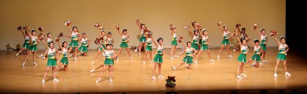 チアダンス発表会でポーズを揃える女子小学生